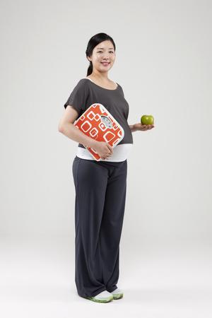 Aziatische zwangere die vrouw met appel en schaal op wit wordt geïsoleerd