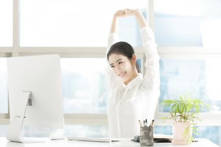 Femme d & # 39 ; affaires asiatique faisant le bras étirement dans le bureau Banque d'images - 87633286