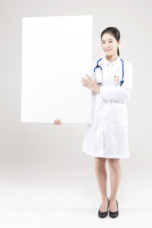 Asian female doctor with white board isolated on white
