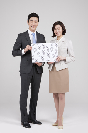 Asian business couple with light bulb drawing isolated on white