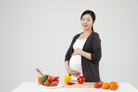Asian pregnant woman with fresh food isolated on white