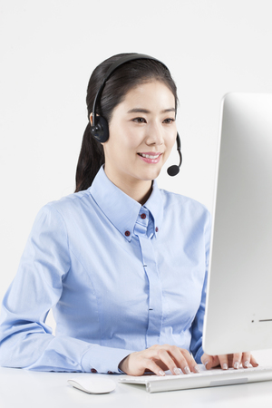 Asian female telemarketer with desktop isolated on white Stock Photo