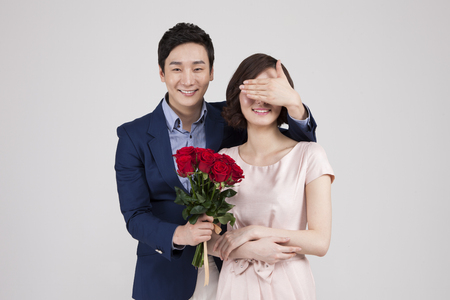 Asian business couple with surprise bouquet isolated on white