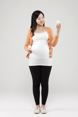 Asian pregnant woman with baby bottle isolated on white