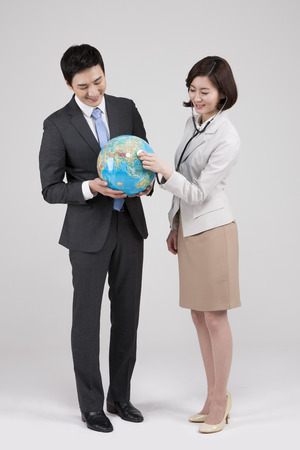 Asian business couple with globe isolated on white