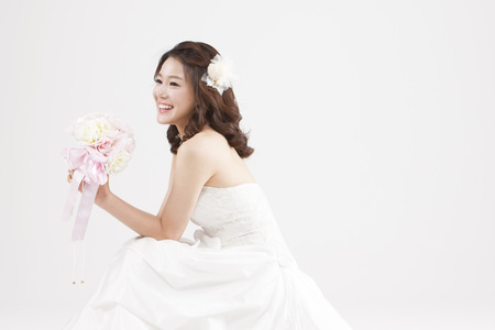 Asian beautiful bride with bouquet isolated on white Imagens