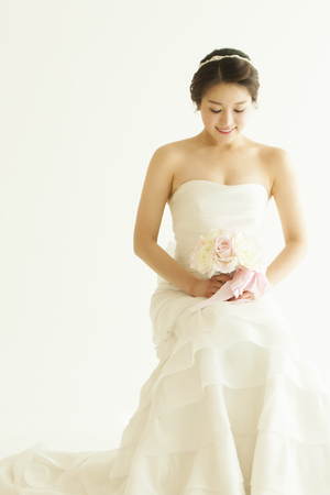 Asian beautiful bride with bouquet isolated on white Banco de Imagens