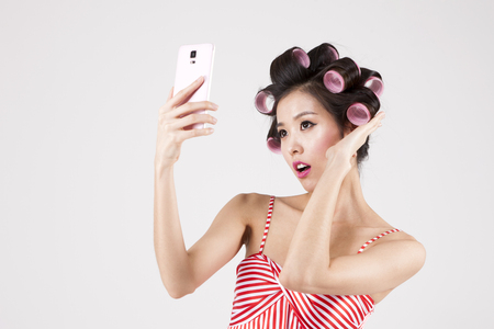 Asian retro woman in curlers taking a selfie isolated on white