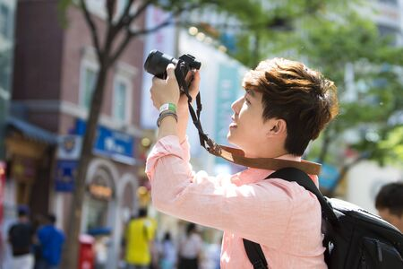 Asian tourist woman taking a picture in Seoul city street