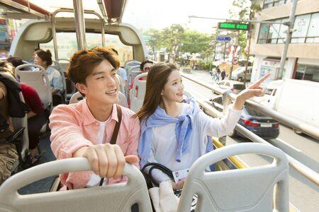 Asian tourist couple enjoying tour bus