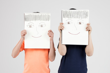 Asian elementary school students with face drawing isolated on white