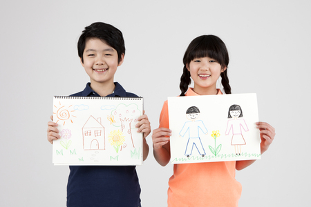 Asian elementary school students with drawing isolated on white