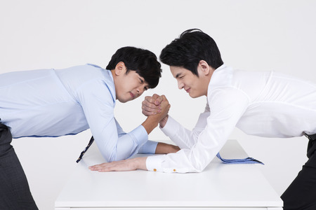 Asian business two men playing arm wrestling isolated on white Stock Photo