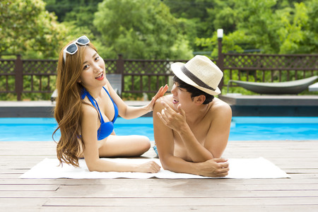 Asian happy couple in swim wear enjoying summer vacation day at pool Stock Photo