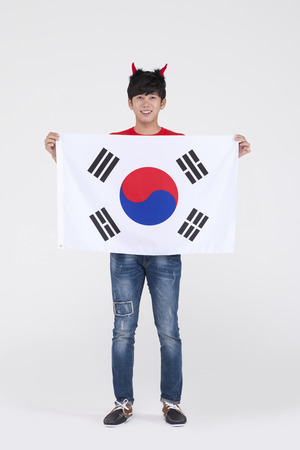 Asian young man with Korea flag to cheer for soccer team isolated on white