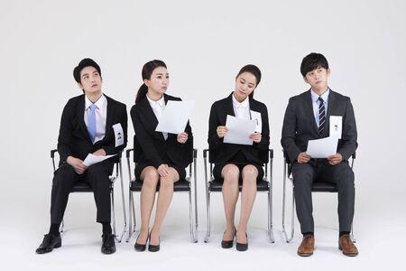 Asiatische Leute, die auf das Vorstellungsgespräch lokalisiert auf Weiß warten Standard-Bild