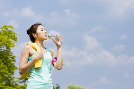 스카이와 아시아 스포티 한 여자 마시는 물