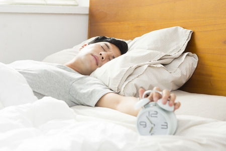 Wake up of Asian young man on bedroom