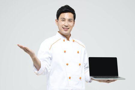 화이트 절연 노트북과 아시아 남성 요리사