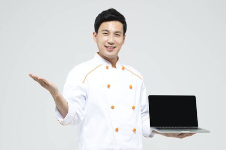 Asian male chef with laptop isolated on white