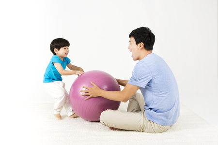 Asian father and son playing with gym ball isolated on white Stock Photo