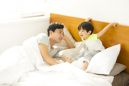 Asian father and son having fun on bedroom Stock Photo