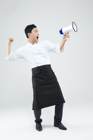 loudspeaker: Asian male chef shouting with loudspeaker isolated on white