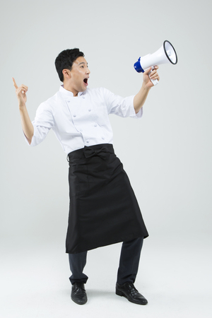 loudspeaker: Asian male chef with loudspeaker isolated on white Stock Photo