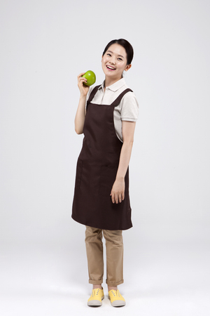 Young Asian woman in apron posing with a green apple - isolated on white