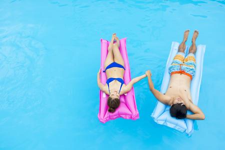 woman bath: Asian young couple in swim wear having fun at pool