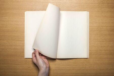 Hand draaiende pagina van notitieboekje op houten lijst