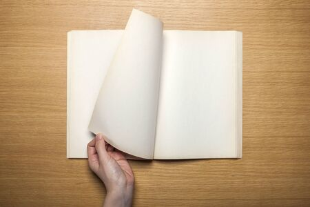 Hand turning over page of notebook on wooden table
