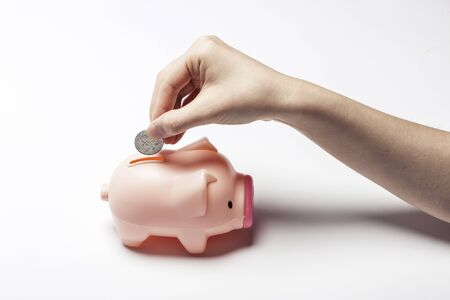Putting coin into piggy bank isolated on white Stock Photo