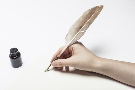 Hand writing with feather quill isolated on white