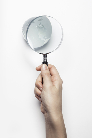 Hand holding magnifier isolated on white
