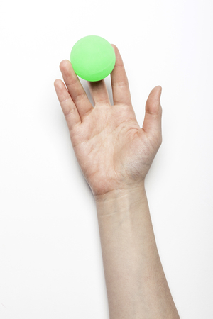 Hand holding ping pong ball isolated on white
