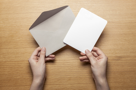 Hand holding Grey envelope and paper on wooden table