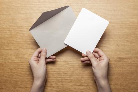 Hand met grijze envelop en papier op houten tafel