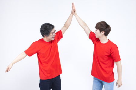 Asian father and son giving high five isolated on white