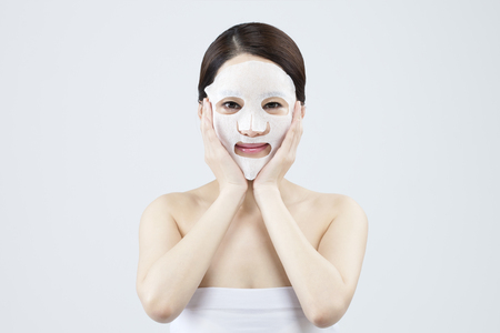 Asian beautiful woman with facial mask isolated on white