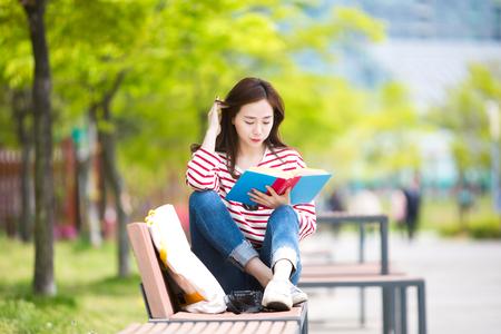 Asian beautiful woman reading book outdoor