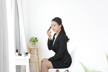 Asian woman doing make up