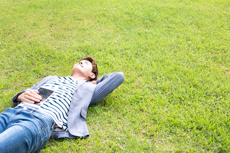 Asian young man lying on grass