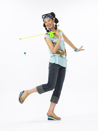 Stylish Asian girl with snorkle goggles holding a plastic fishing rod and posing in the studio - isolated on white Stock Photo