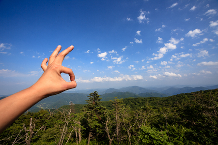 republic of korea: Hand making an okay sign with the mountains in the background