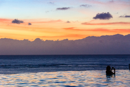 Silhouette of girls swimming with the sunset in the background