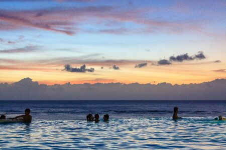 Silhouette of people swimming with the sunset in the background