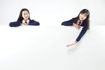 아시아 여성 고등학교 학생은 흰색에 고립 된 벽 뒤에