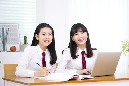 Asian female high school students using laptop