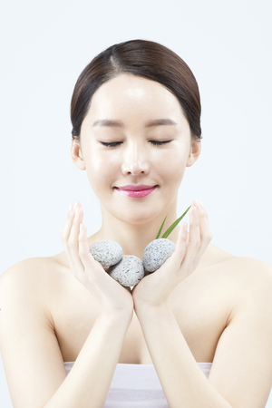 Asian beautiful woman with stones isolated on white Stock Photo